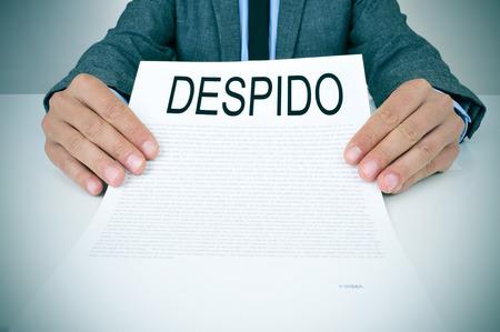 een jonge blanke zakenman in grijs pak zittend aan zijn bureau toont een document met de tekst despido, ontslag in het spaans, geschreven erin Stockfoto