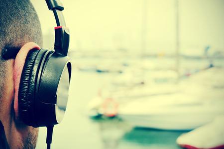 Gros plan d'un jeune homme écoute de la musique avec un casque en face de la mer dans un port de plaisance, avec un effet de filtre Banque d'images