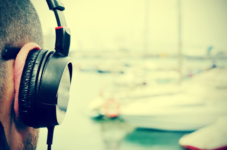 oir: Primer plano de un hombre joven escuchando música con auriculares en frente del mar en un puerto deportivo, con un efecto de filtro Foto de archivo