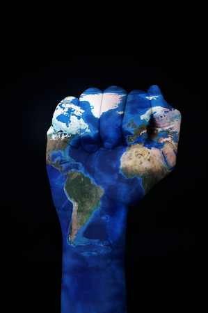 black empowerment: the raised fist of a young man patterned with a world map (furnished by NASA) on a black background depicting the concept of the ecologist movement or the empowerment of the ecologism