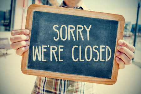 sorry: closeup of a young caucasian man wearing a plaid shirt shows a chalkboard with the text sorry we are closed written in it, with a filter effect Stock Photo