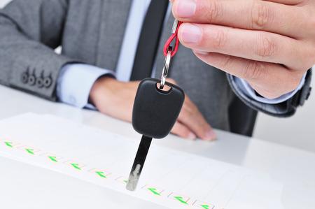 een jonge blanke man in een grijs pak zittend aan zijn bureau geeft een autosleutel aan de waarnemer