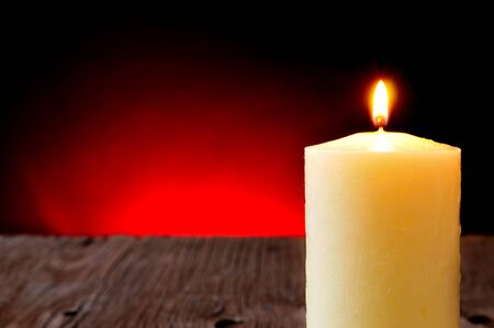 lit candle: closeup of a lit candle on a wooden rustic table and a red lighted background