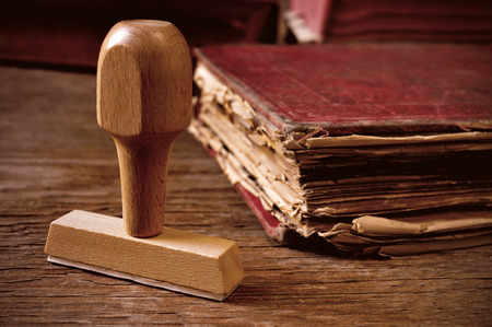 record shop: closeup of a rubber stamp and a worn-out old book, on a rustic wooden table Stock Photo