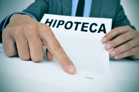 signer: young caucasian man wearing a grey suit sitting at his office desk showing a document with the word hipoteca, mortgage loan contract in spanish, and where the signer must sign