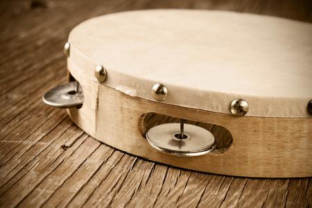 pandero: primer plano de una pandereta en una mesa de madera rústica, procesamiento pesado para look retro blanqueada