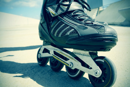 rollerskating: closeup of the feet of a young man roller skating with inline skates, with a slight vignette added