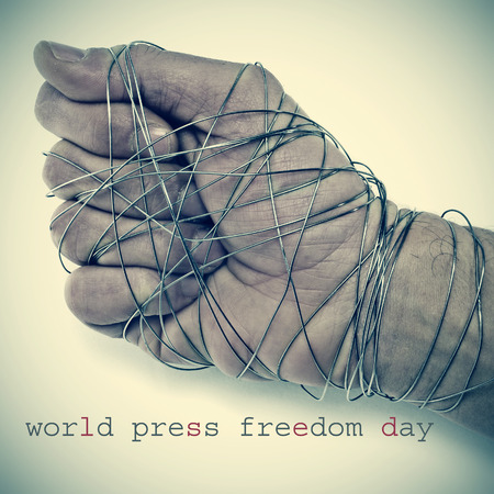 repression: the text world press freedom day and the hand of a man completely tied with wire, depicting the idea of oppression or repression