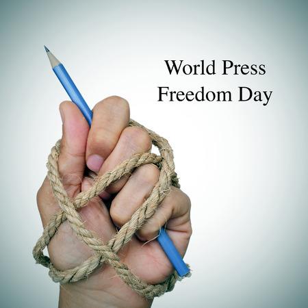 el mundo de texto la libertad de prensa día y la mano de un hombre, completamente atado con una cuerda, sosteniendo un lápiz, que representa la idea de la opresión o represión Foto de archivo