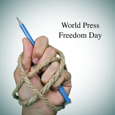 the text world press freedom day and the hand of a man, completely tied with rope, holding a pencil, depicting the idea of oppression or repression Stock Photo