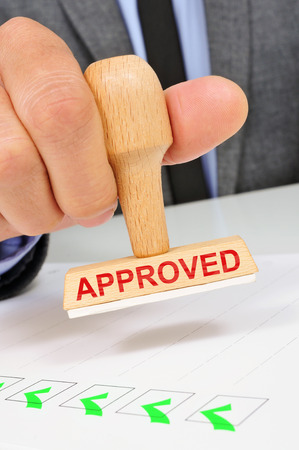 approbation: a young caucasian man at his office desk with a rubber stamp with the word approved