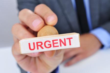 hombre caucasico: un hombre cauc�sico joven en su escritorio de oficina con un sello de goma con la palabra urgente