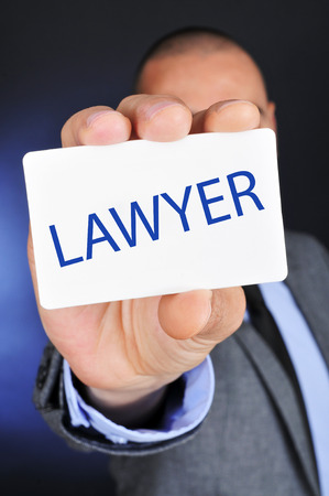 litigate: a young caucasian man wearing a gray suit shows a signboard with the word lawyer written in it
