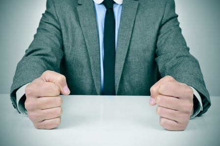 demotion: closeup of a young caucasian man wearing a gray suit banging his fists on his office desk Stock Photo