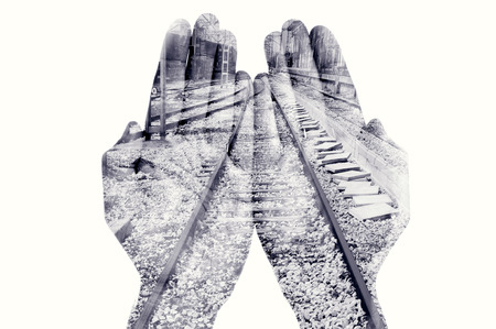 put together: double exposure of the palms of a man put together and a railway, in black and white