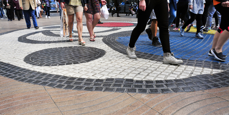 rambla: Barcelona, Spain - April 20, 2015: People stepping on the Pla de lOs mosaic in La Rambla in Barcelona, Spain. Thousands of people walk daily on the mosaic, designed by famous Joan Miro