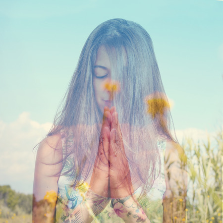 anjali: double exposure of a young brunette woman meditating and a peaceful landscape with yellow flowers