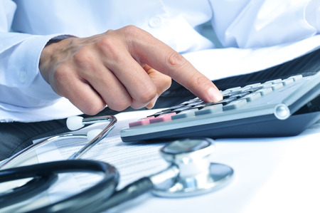 calculadora: primer plano de una joven caucásica profesional de la salud que lleva una bata blanca calcula en una calculadora electrónica Foto de archivo