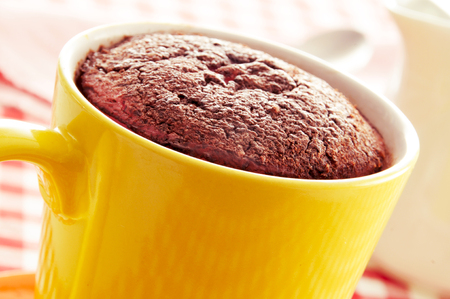 cup cakes: closeup of a chocolate mug cake in a yellow porcelain mug on a set table covered with a checkered tablecloth