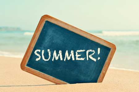 closeup of a chalkboard with a wooden frame and the word summer written in it, placed on the sand of a beach