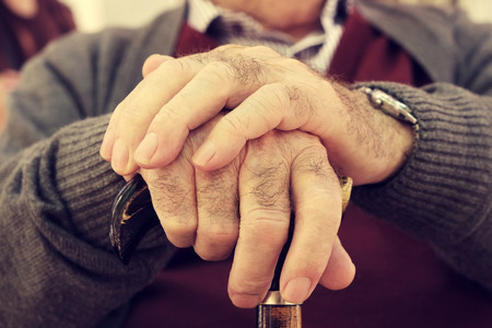 gerontology: closeup of the hands of an old caucasian man with a walking stick