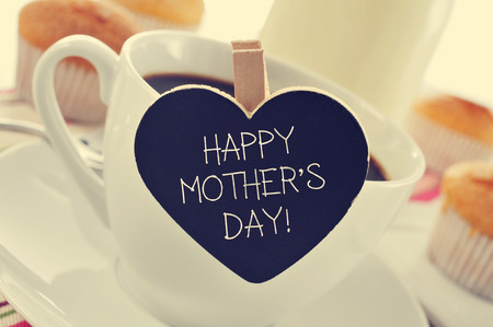 mothers day: the sentence happy mothers day written in a heart-shaped blackboard placed in a cup of coffee, with some muffins in the background in a set table for breakfast