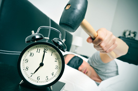 stressing: a young caucasian man in bed about to hammer his alarm clock at seven in the morning Stock Photo