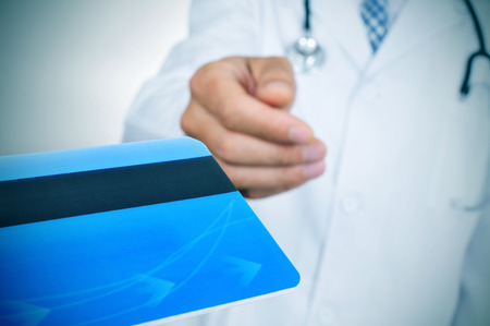 geriatrician: closeup of a young caucasian doctor accepting a blue credit card Stock Photo