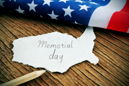 armed services: a piece of paper in the shape of United States with the word Memorial Day written in it, placed on a wooden background next to the flag of the United States