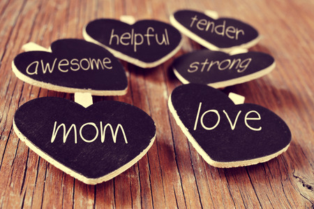 motherly: some heart-shaped blackboards with concepts referring to a good mom written in them, such as love, helpful, awesome, tender or strong, placed on a rustic wooden surface Stock Photo