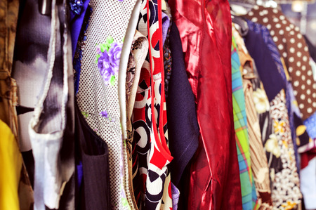 used clothes: some different used clothes hanging on a rack in a flea market Stock Photo