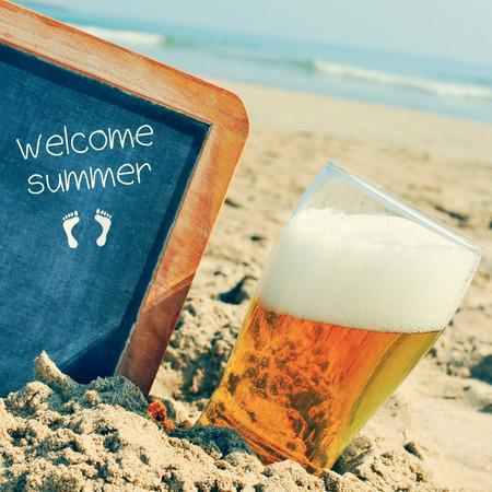 acogida: primer plano de un vaso de cerveza refrescante y una pizarra con un marco de madera y el texto de bienvenida del verano escrito en ella, colocada sobre la arena de una playa