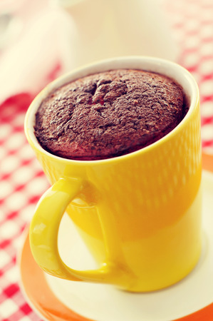 Gros plan d'un gâteau de tasse de chocolat dans une tasse de porcelaine jaune sur une table de jeu recouverte d'une nappe à carreaux