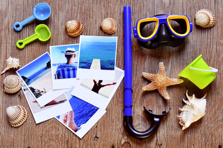 high-angle shot of rustic wooden table full of summer stuff, such as different conches, seashells and starfish, a diving mask and a snorkel, beach toys and some photos, shot by myself, of beach scenes photo
