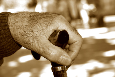 expectancy: closeup of the hand of an old caucasian man with a walking stick, in sepia toning