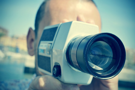 film: closeup of a young caucasian man filming with a retro film camera outdoors Stock Photo