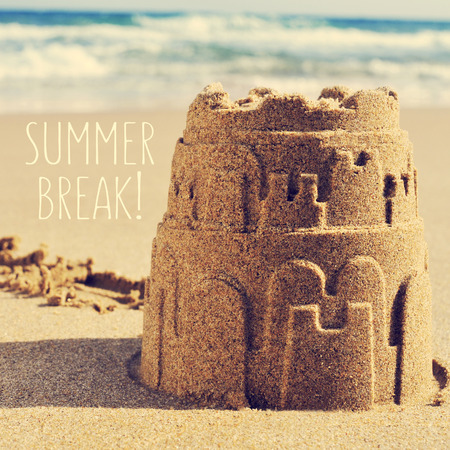 a sandcastle on the sand of a beach and the text summer break Stock Photo