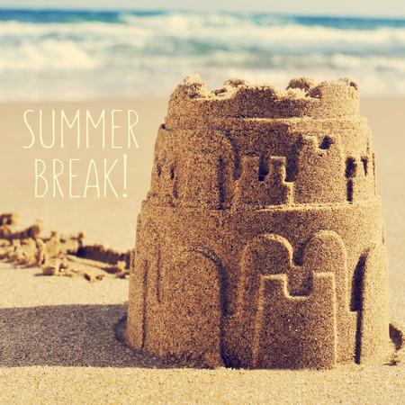castillos: un castillo de arena en la arena de una playa y las vacaciones de verano de texto Foto de archivo