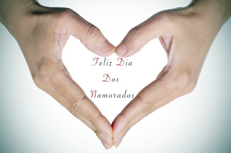congratulate: woman hands forming a heart and the text Feliz Dia Dos Namorados, written in portuguese, to congratulate for the holiday for lovers in Brazil Stock Photo