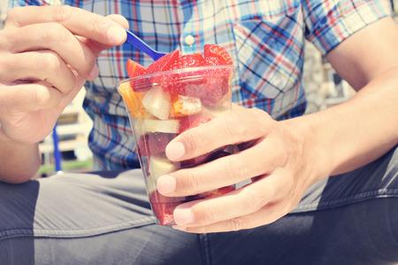 ensalada de frutas: Primer plano de un hombre caucásico joven que llevaba una camisa a cuadros de comer una ensalada de frutas en un vaso de plástico transparente al aire libre