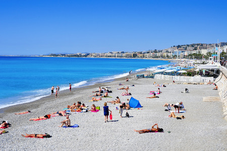 sun bathers: Nice France  May 16 2015: People sunbathing on the beach in Nice France. The long and famous seafront of Nice bordering the Mediterranean Sea is known as the Promenade des Anglais Editorial