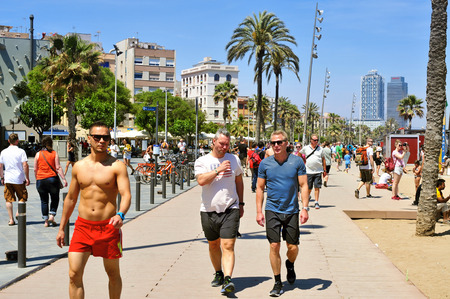 seafront: Barcelona Spain  May 28 2015: A crowd of people walking in the seafront of La Barceloneta in Barcelona Spain. The city has a long and busy seafront