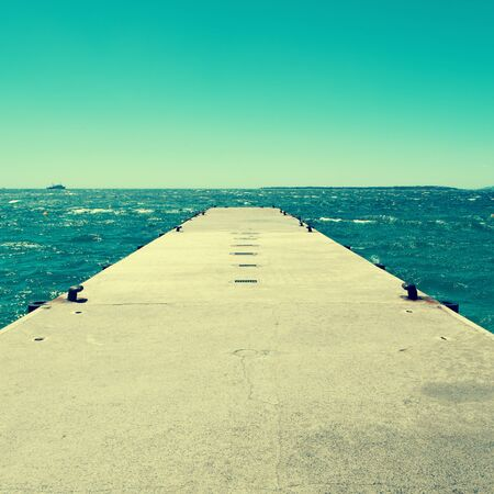 mooring bollards: picture of a concrete dock with some mooring bollards in the Mediterranean sea, with a retro effect Stock Photo