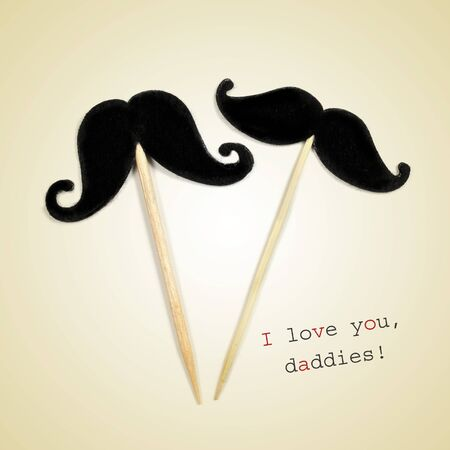 moustache: the text I love you daddies and two moustaches glued to wooden toothpicks on a beige background Stock Photo
