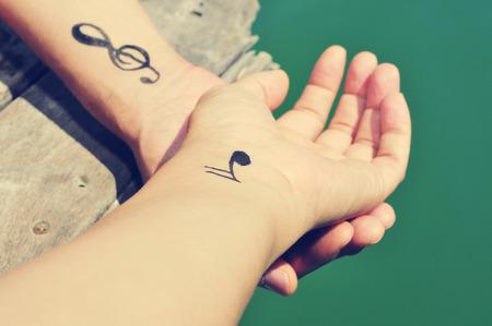 armonia: primer plano de un hombre caucásico joven con algunos símbolos musicales tatuados en sus muñecas, pasando el rato en un muelle de madera en el mar Foto de archivo