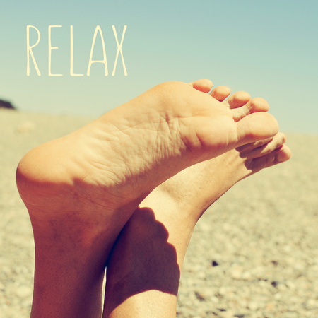 beach feet: the text relax and the bare feet of a young caucasian man relaxing in a shingle beach, with a retro look Stock Photo