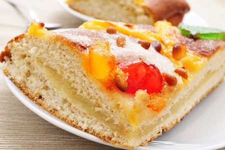 juan: closeup of a piece of coca de Sant Joan, a typical sweet flat cake from Catalonia, Spain eaten on Saint Johns Eve, on a plate