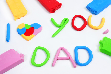 red clay: the text I love you dad made from modeling clay of different colors Stock Photo