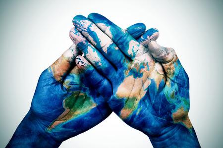 de handen van een jonge man samen patroon met een kaart van de wereld, lichte vignet toegevoegd Stockfoto