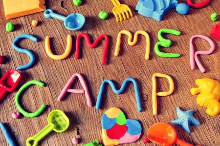 다양한 색상과 같은 장난감 삽과 모래 금형 등 일부 해변 장난감의 모델링 점토로 만든 텍스트 여름 캠프, 소박한 나무 표면에